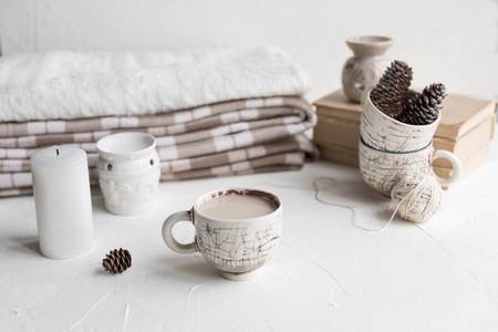 A cup of coffee with milk and a cosy wool plaid on the white concrete table in the morning. Winter or autumn season. Stock Photo