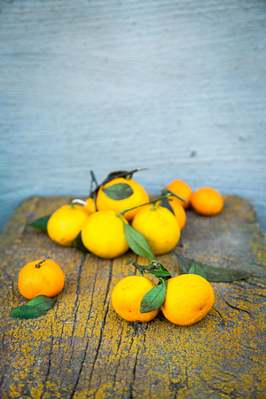 Some fresh mandarins on old wooden background, dry leaves and some peels and cloves.