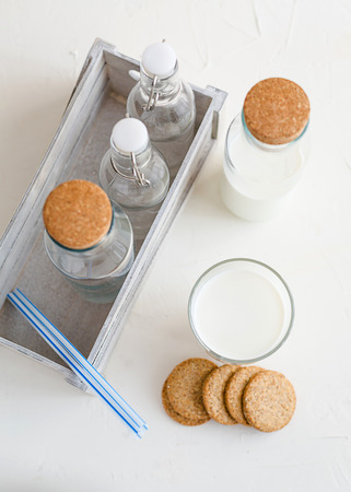 Some fresh milk in glass bottles and decorated with kitchen napkin and a box-keeper.