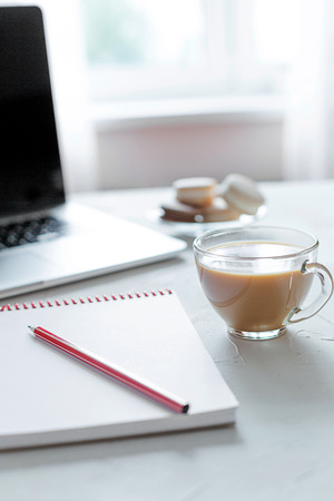 Open lap-top and a note, office table. Morning time. Beginning of the working day