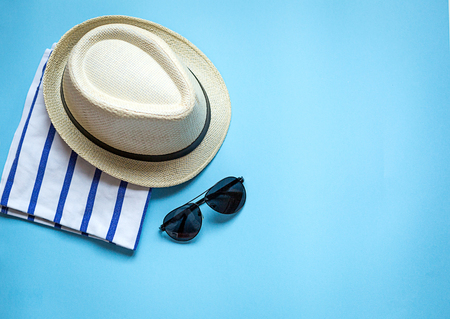 Straw hat, sunglasses, stripped towel, camera, cyan paper background