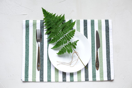 Table setting with stripped coton napkin, knife and fork.Decorated with green leaf
