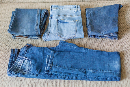 Several folded denim clothes are on the sofa. Shades of blue denim fabric.