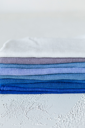 A pile of blue colored palette gauze on white concrete background. Textile, natural material. Copy space, shelf in the market. Stock Photo