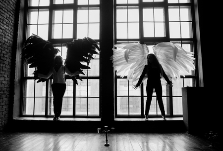 Two young girls with long hair and angel wings are in front of the window. Black and white picture. Symbol of love.