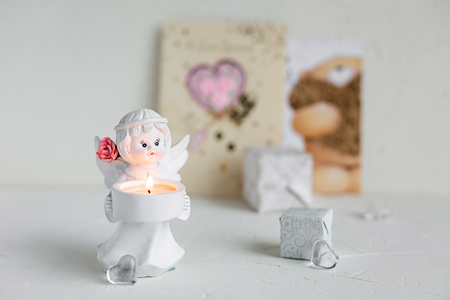 Still life of small angel candleholder with lighted candle and boxes, glass hearts on white concrete background. Holiday concept, greeting card. Imagens - 114431078