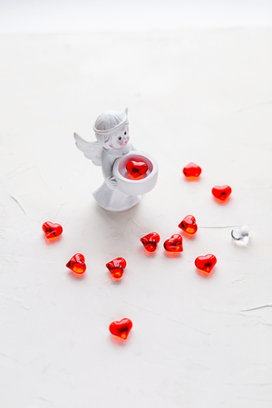 Small statuette of an angel with red plastic hearts on white concrete background. St. Valentines holiday, greeting card. Banco de Imagens