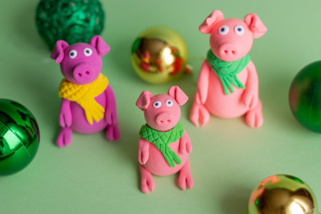 Hand made little plasticine pigs on colorful paper background. Symbol of a chinese new year and chinese holiday concept.