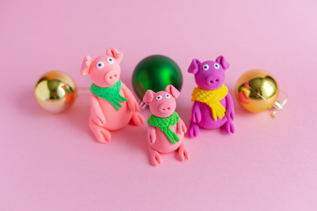 Three hand made little plasticine pigs on pink paper background. Symbol of a chinese new year and chinese holiday concept.