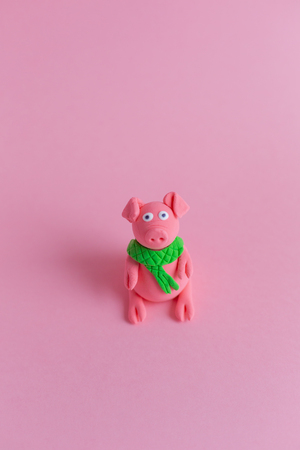 Hand made little plasticine pig on pink paper background. Symbol of a chinese new year and chinese holiday concept.
