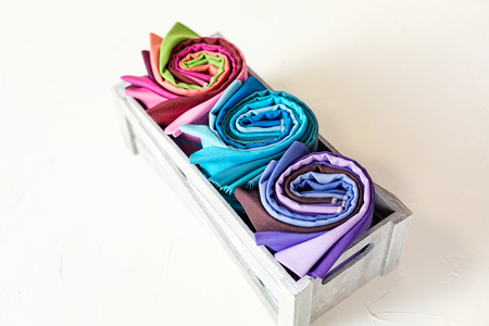 Rolled up colorful fabric are in a grey wooden box on white background.