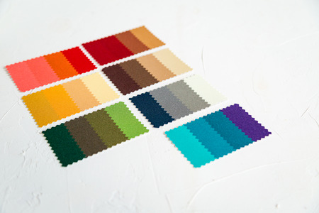 Top view of colorful felt swatches on white concrete table. Image maker of stylist instrument for color type determination.