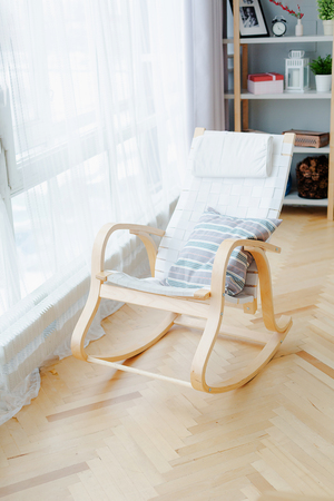 White rocking chair in a room of light and bright style in daylight. Home cosy interior. Banco de Imagens