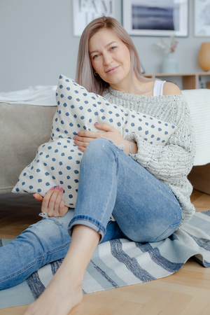 A blonde woman in a cozy woolen sweater is sitting near the big bed on the floar and holding a pillow. Morning time. Reklamní fotografie