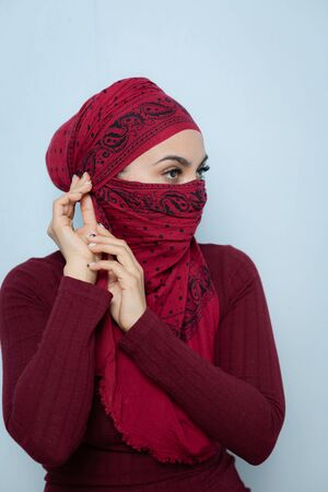 A young handsome muslim woman ties the red handkerchief.