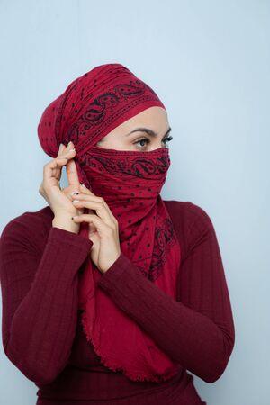 Una giovane bella donna musulmana lega il fazzoletto rosso. Archivio Fotografico