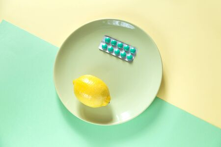 Mix of treatment on two color background. Some pills and a lemon on the plate. Green and yellow colors.