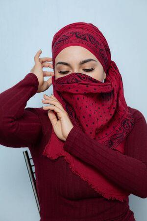 A young handsome muslim woman ties the red handkerchief. Archivio Fotografico - 129217874