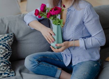 A young blonde woman with long hair holds a vase with purple peonies. Decoration of a home interior or preparation for the holiday.