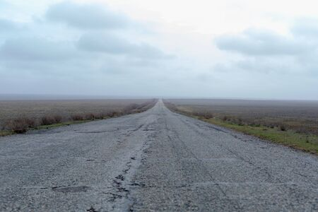 Wide old road in the foggy steppe in spring early morning. Archivio Fotografico