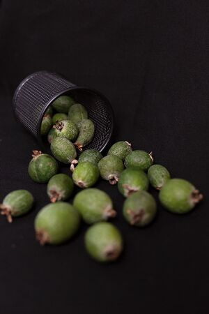 Raw of fresh and ripe  green feijoa in a metal jar on black textile background. Healthy and season food.