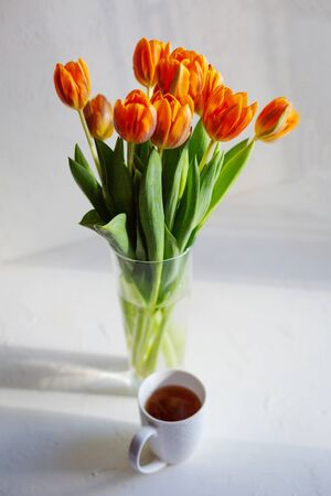 Spring orange tulips in a vase  and a cup of hot tea or coffee on the white table near the window.