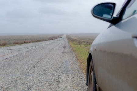 A dirty car on the road in a wild steppe in spring early morning.