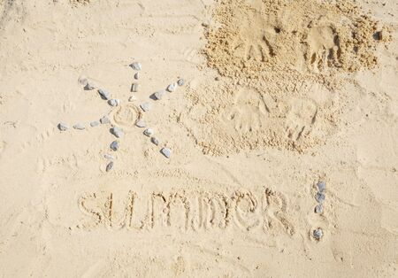 Top view of summer sand drawing . The sun and text Summer and two child handprint are on the sand. Stock fotó