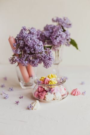 Purple spring lilac flowers still life  with candies on white background in the morning.