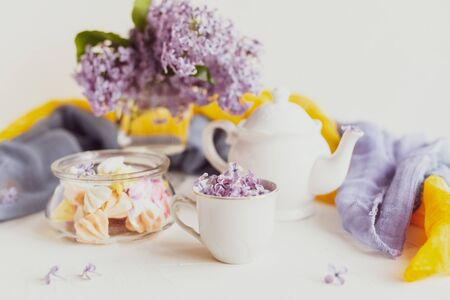 Purple spring lilac flowers still life on white background in the morning. Tea-time or breakfast with black tea and candies.