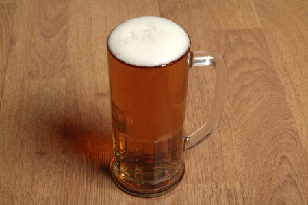 Single beer glass on wooden table background photo