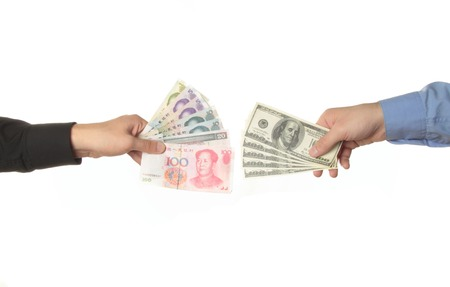 Hands holding yuan and dollar bills isolated photo