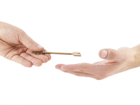 golden key: Male hand holding golden key Stock Photo