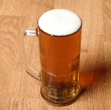 alehouse: Single beer glass on wooden table Stock Photo