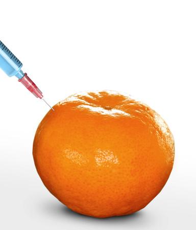 genetically engineered: syringe sticked into orange,GMO