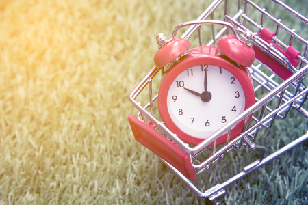Red clock on the shopping cart, lack of time, waste of time, purchasing time