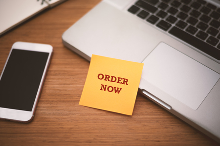 Order Now text on post it paper near laptop and smart phone on wood table, Online shopping and Technology marketing concept. Stock Photo