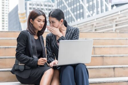 Business women gossip while using laptop at outdoor. Business and coworker concept Stock Photo