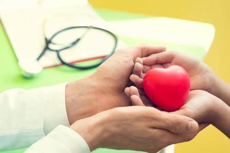 Hand of doctor give red heart to little patient children for recover from sickness. Hospital and Healthcare concept.