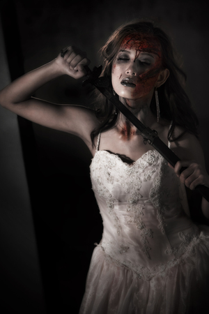 Zombie lady corpse holding sword to kill herself while wedding. Horror and Ghost concept for Halloweens day theme event. Dark and grunge tone film