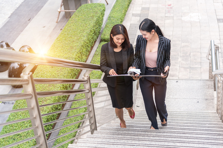 Two business women waking up on stair and talking together. Business and work concept Stock Photo