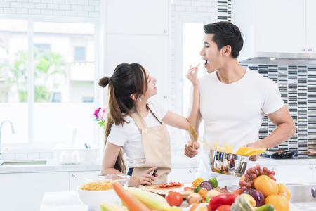 Asian Lovers feeding fruit and food to each other, Couple and Family concept. Honeymoon and Holidays theme. Indoor interior