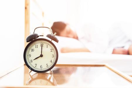 Wekker met slapende vrouw in bed kamer. Luie tijd in vakantieconcept.