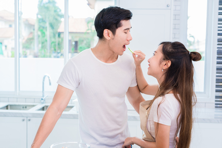 Woman feeding cucumber to man as Lovers or couples in kitchen room. Cooking and Honeymoon and wedding concept