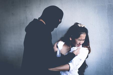 Un ladrón obliga a una mujer a quitarse la ropa en una casa abandonada. Tema de violación y criminal. Problemas sociales y concepto de problema.