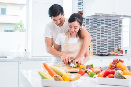 Asian lovers or couple cooking and slicing vegetable in kitchen room. Man and woman looking each other in home. Holiday and Honeymoon concept. Valentine day and wedding theme