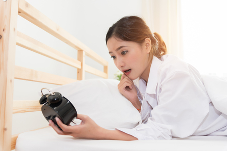 Asian woman shocked when wake up by alarm clock because too late for meeting appointment or working. Lazy day and Hurry up concept.