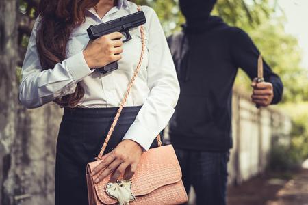 Cerrado de mujer que oculta la pistola de mano en el frente para luchar contra el ladrón o protegerse de robar su dinero o peligroso. Concepto de violación sexual y sexual. Informe de noticias y tema de desaceleración económica