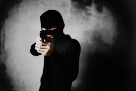 Terrorist shooting with his mini gun weapon with grunge room wall background. Criminal and Dangerous illegal people concept. Terrorist and war theme. Dark tone and high contrast use Banco de Imagens