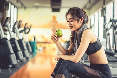 Mulher asiática que guarda e que olha a maçã verde para comer com material desportivo e escada rolante no fundo. Comida limpa e saudável conceito. Treino de fitness e tema em execução.